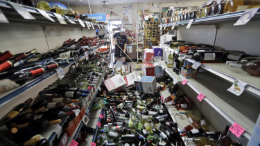 Bottles of wine are strewn in the middle of an aisle as Victor Abdullatif mops inside of his family's store in Ridgecrest.
