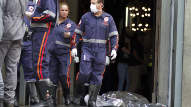 A firefighter walks next to a victim killed at the Metropolitan Cathedral in Campinas, Brazil, on Tuesday.