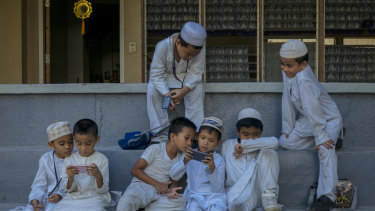 Students in a Muslim school play with their mobile devices in Zamboanga.