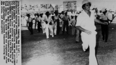 Scan from AP radiogram image in the SMH Archive. Australian opening batsman, Graeme Wood leads the way as members of the Australian team and policemen run for shelter from bottles and stones hurled by spectators at Sabina Park May 3 the Fifth Day of play in the Test Match between Australia and the West Indies.