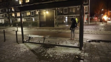 A person stands at a bus stop where the glass has been shattered after rioting, in Haarlem, Netherlands.