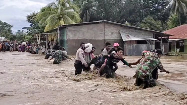 Soldiers and police officers assist residents to cross a flooded road in Malaka Tengah, East Nusa Tenggara province, Indonesia.