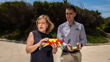 Lisa Neville and Kane Treloar holding a Lifesaving Victoria drone at a beach in Ocean Grove.