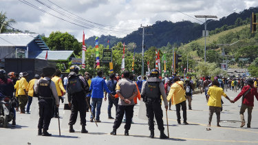 Police officers stand guard as protesters march during a rally in Abepura, Papua province, Indonesia.