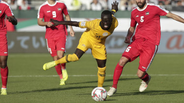 Socceroos winger Awer Mabil and Palestine defender Tamer Salah fight for the ball.