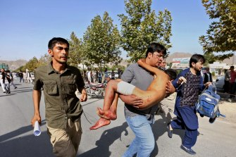 An injured boy is carried to a hospital after an explosion struck a protest by members of Afghanistan's largely Shia Hazara ethnic minority group in 2016.