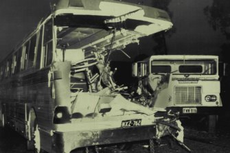 The wrecked tourist coach with the semi-trailer in the background. The impact sheared off the coach's left side.