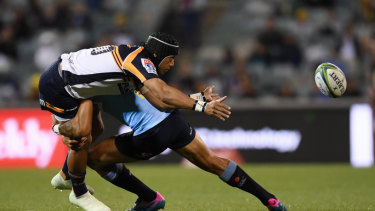 Back in the fold: Christian Lealiifano gets a pass away for the Brumbies despite the attention of Israel Folau.