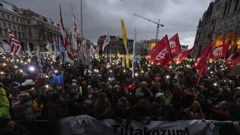 """Anti-government demonstrators carry a banner reading """"We protest against the slave bill"""" as they protest in front of the Parliament building at Kossuth square in  Budapest on  Saturday."""