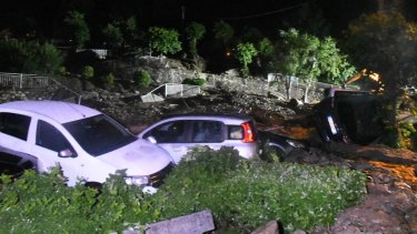 Capsized cars as seen the roads of after they were hit by a landslide in Casargo, near the northern Italian town of Lecco.
