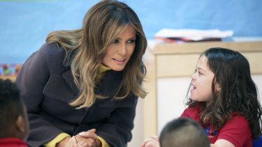 Melania Trump talks with a pre-kindergarten student during a visit to a Tulsa school.