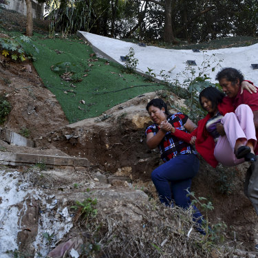 Flory Teletor, a victim of gun violence, needs to be carried up the steps to the street above her sister and brother-in-law's house in Guatemala City.