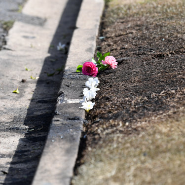 Flowers are left at the scene of the car fire.