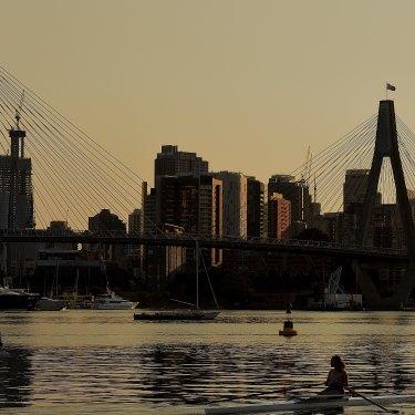 Smoke haze lingers over Sydney as rowers train in Rozelle Bay early on December 4.