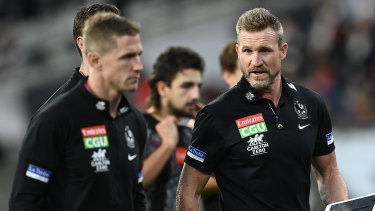 Magpies coach Nathan Buckley talks to his coaching staff during the Anzac Day clash with Essendon at the MCG.