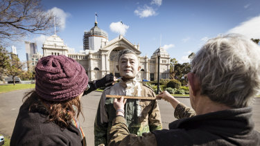 Now you see him: Liu Bolin's team works to camouflage him at the Royal Exhibition Building on Monday.