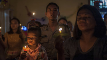 People attend a Christmas service at Rahmat Pentecostal Church in Carita.