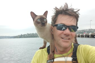 Gus the cat, winner of his category in the Scotland Island dog race with his owner Glenn Druery.