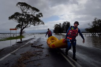 An SES crew carries their boat from the floodwaters that have partially submerged Bolong Road at Shoalhaven Heads.