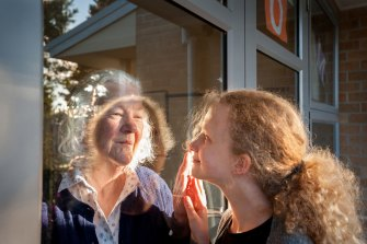 Margaret Wheeler greets her granddaughter Alice through the glass of her aged care facility in Victoria last year.