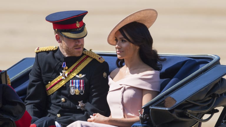 Prince Harry, and Meghan, the Duke and Duchess of Sussex ride in a carriage during the Trooping the Colours ceremony at Horse Guards Parade as the Queen celebrates her official birthday, in London, on Saturday.