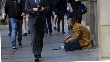The haves and have not ... a man begs in Collins Street, Melbourne.