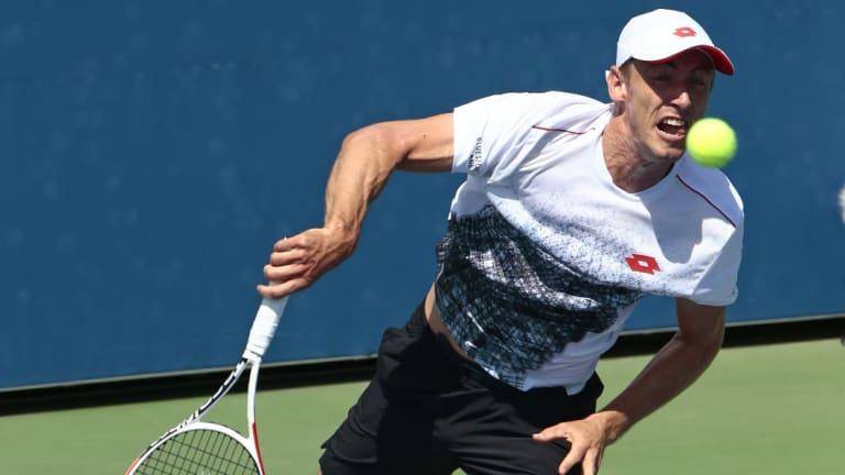 Progress: Australia's John Millman serves to Fabio Fognini, during their second round clash.
