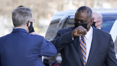 Defence Secretary Lloyd Austin, right, greets Deputy Secretary of Defence David Norquist as he arrives at the Pentagon.