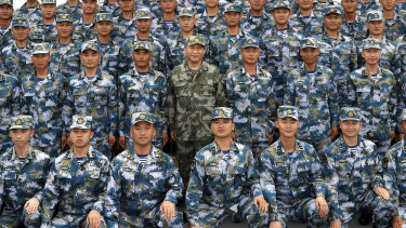 Chinese President Xi Jinping poses with soldiers on a navy ship after he reviewed the Chinese People's Liberation Army Navy fleet in the South China Sea.
