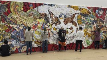 Staff at Takashi Murakami's studio in Saitama, Japan, work on the detailed decorative surface of Murakami's new work for the Art Gallery of NSW.