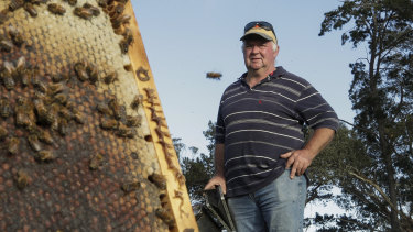 Laurie Kershaw with bees on his property in Sutton, NSW. He had to relocate 2500 of his hives during the summer bushfires.