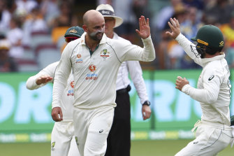 Australia's Nathan Lyon, left, is congratulated by teammate Matthew Wade after taking the wicket of India's Rohit Sharma during play on day two of the fourth cricket test between India and Australia at the Gabba,
