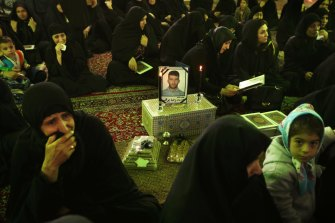 Women surround a framed photo of asylum seeker Reza Berati, during the memorial service held at the Al-Mahdi mosque in the Nabard neighbourhood in South East Tehran, Iran. 27th Feburary, 2014. Photo: Kate Geraghty
