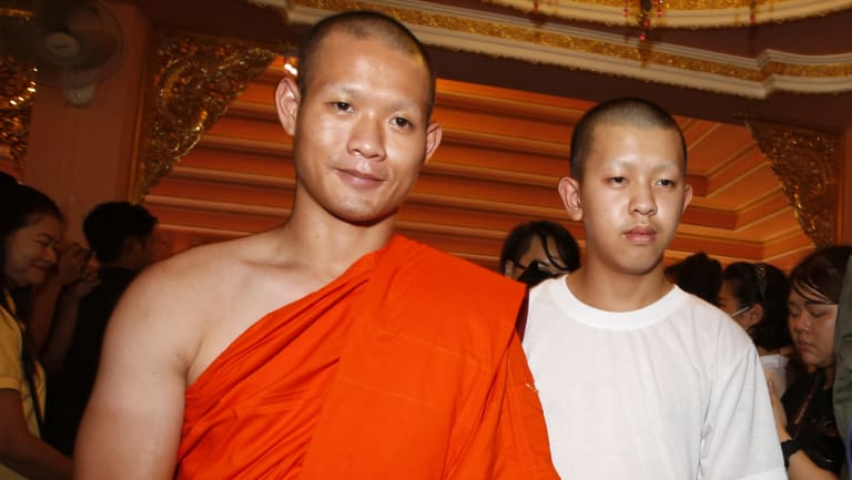Monk Ekkapol Chanthawong walks with Pornchai Kamluang, right, a member of Wild Boars soccer team.