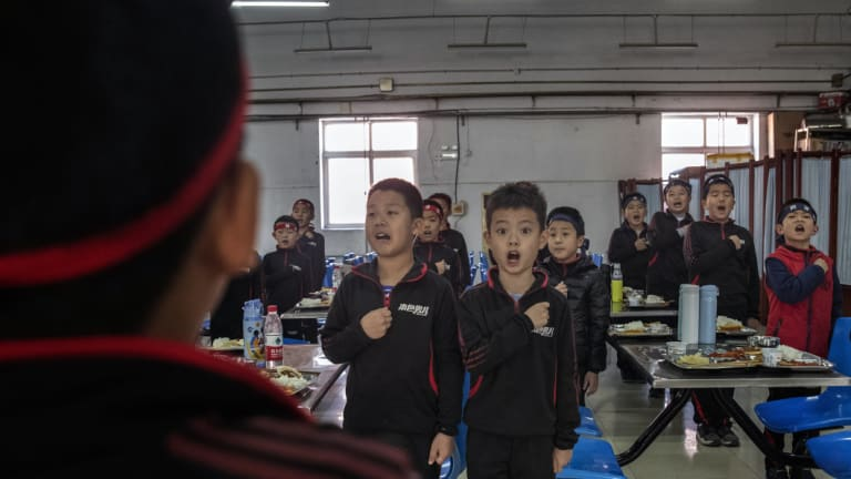 Students at the Real Boys Club in Beijing recite the club's pledge.