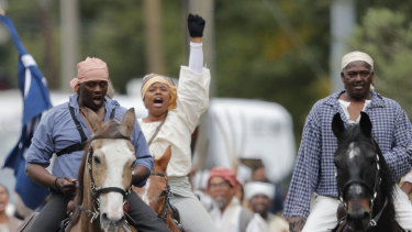 People participate in a performance artwork reenacting the largest slave rebellion in US history in LaPlace, Louisiana.