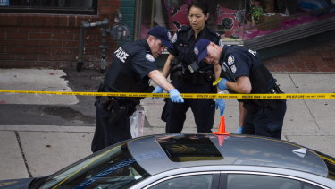 Police investigate a car with a bullet hole within the scene of the shooting.