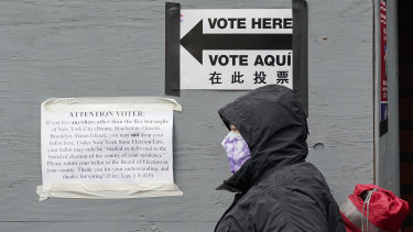 A woman wears a protective mask during the coronavirus pandemic as she stands in line for an early voting location near Lincoln Centre in New York.