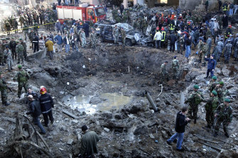 Rescue workers and soldiers stand around a massive crater after a bomb attack that tore through the motorcade carrying Prime Minister Rafik Hariri in Beirut, Lebanon in 2005.