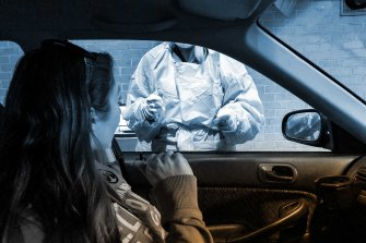 At a drive-through testing centre, a nurse prepares to swab reporter Sherryn Groch for COVID-19.