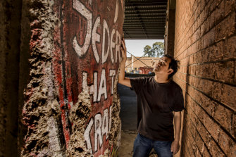 Raymond Chim with the section of the Berlin Wall that sat unknown in a Blacktown warehouse. The side that faced west Germany has graffiti reading 'Everyone is powerful'.