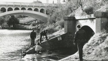Police check a storm water drain on the banks of the Yarra River near the scene of the shooting.