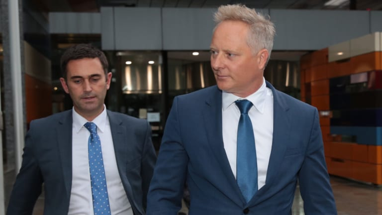 Celebrity financial planner Sam Henderson, right, leaves the Federal Court.