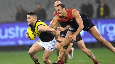 On the burst: Tiger Dion Prestia give Melbourne's Braydon Preuss the slip.