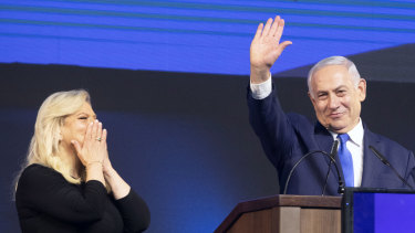 Israel's Prime Minister Benjamin Netanyahu waves with wife Sara at the Likud party HQ in Tel Aviv early on Wednesday morning.
