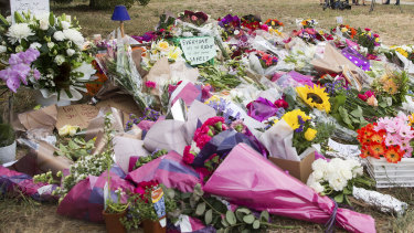 A makeshift shrine continues to grow at the murder scene.