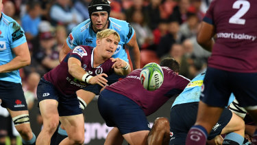 Tate McDermott of the Reds (centre) passes the ball against the Waratahs on May 18.