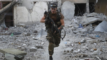 A US-backed Syrian Democratic Forces fighter runs in front of a damaged building as he crosses a street on the front line, in Raqqa, Syria, last year.