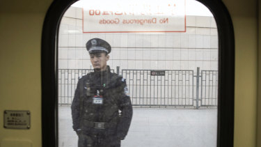 A police officer is seen through a train window in Turpan, Xinjiang, last year.