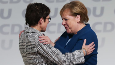 Angela Merkel (lright) congratulates Annegret Kramp-Karrenbauer on becoming the head of Germany's ruling party.
